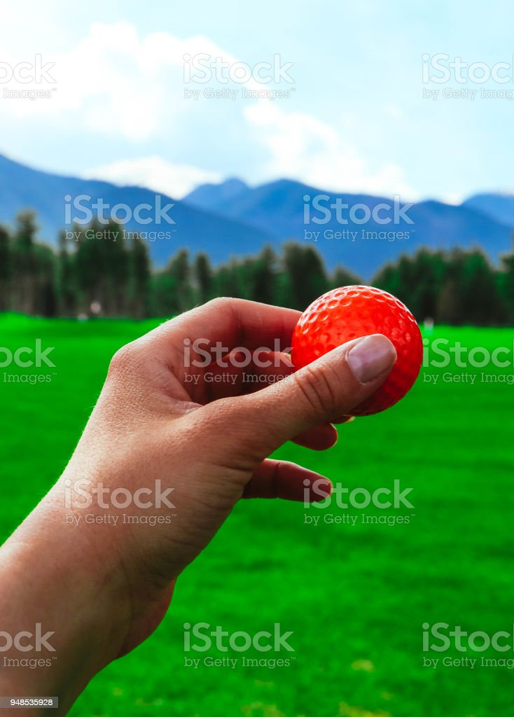 Golf red ball hold in a hand, green course grass, blue sky.