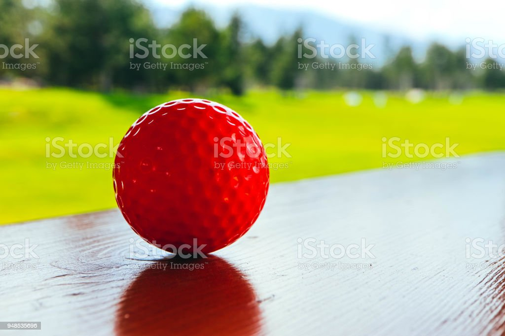 Golf red ball on a wooden surface, green field and blue sky. Macro...