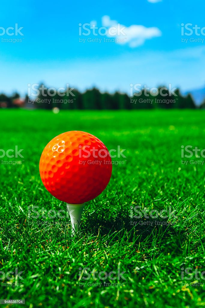 Golf red ball on tee, green grass field, blue sky, macro view.