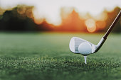 Golf Stick and Golf Ball on Stand on Green Field. Green Grass. Sport in Summer Concept. Outdoor Fun Concept. White Ball. Sunny Day. Sport on Field Concept. Little Ball. Steel Golf Stick.