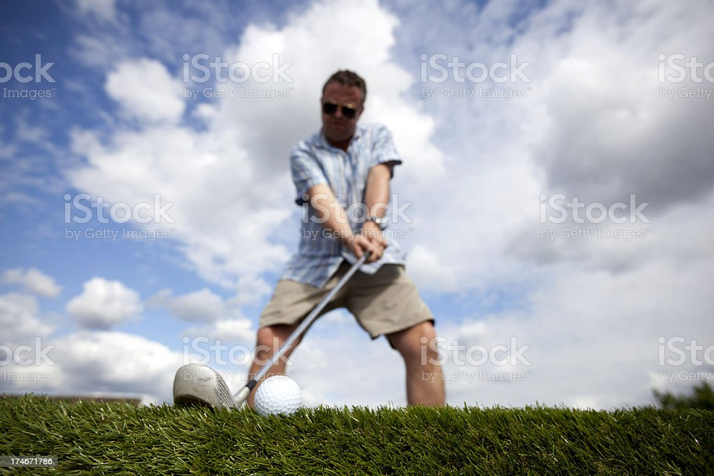 A golfer in shorts prepares to take a shot. Focus on the ball in...