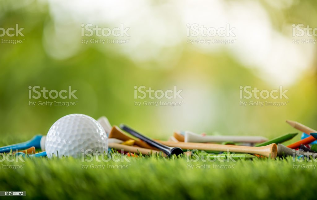 golf tees with ball on green field stock photo