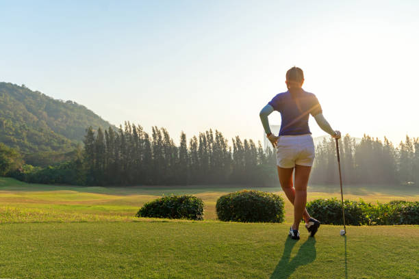 golf women.  cheerful happy asian smiling woman with playing golf in the golf club in the sunny and evening sunset time, copy space. lifestyle concept - female golfer stock photos and pictures