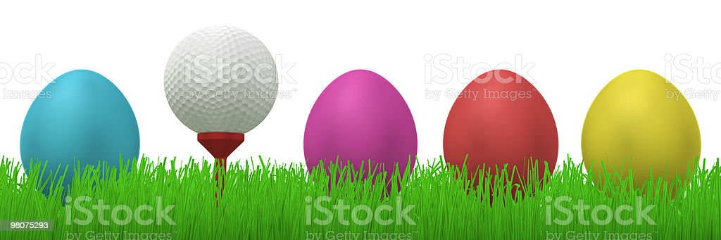 golfball between easter eggs in grass royalty-free stock photo