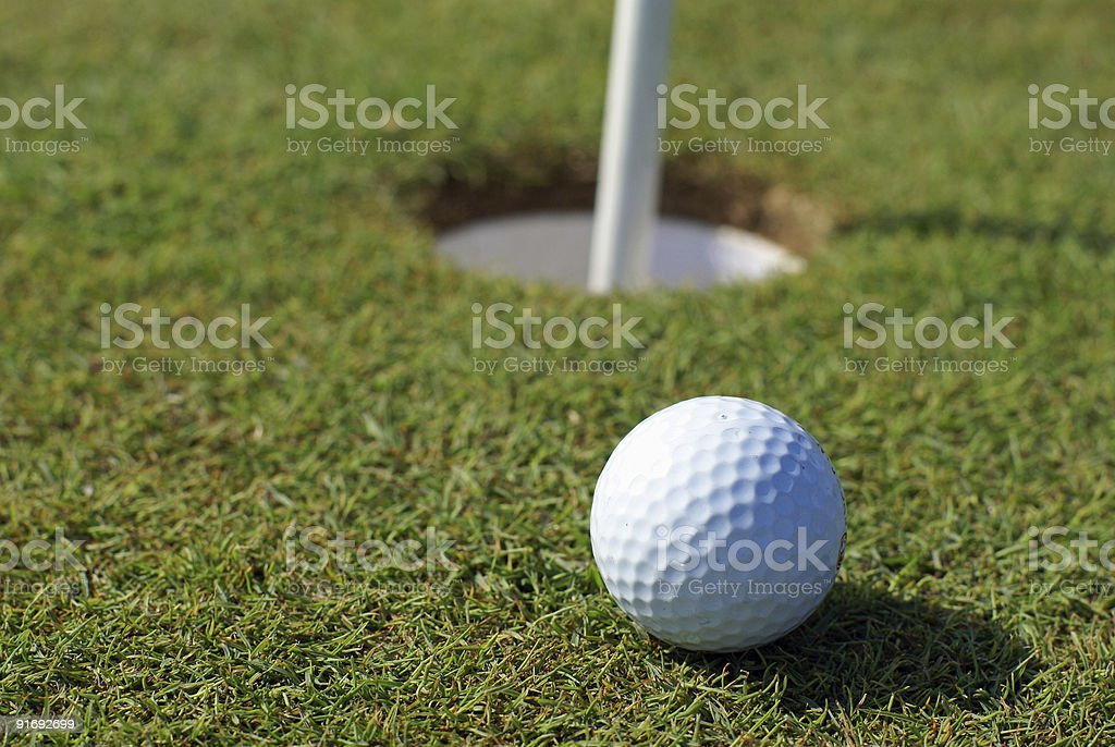 Golfball in front of the hole royalty-free stock photo