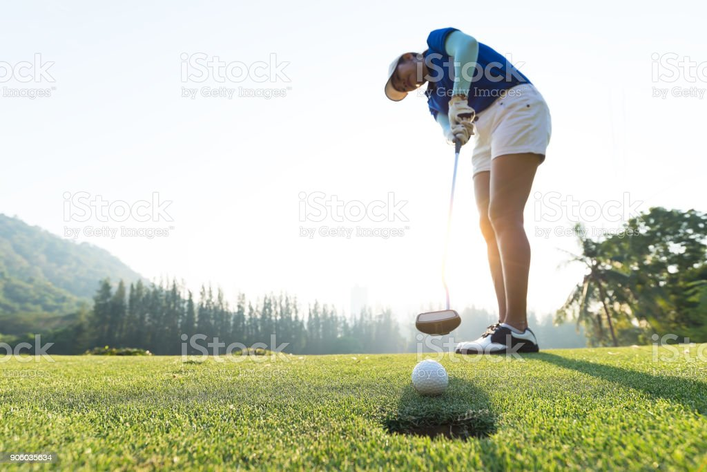 Golfer action to win after long putting golf ball on the green golf. morning time. stock photo