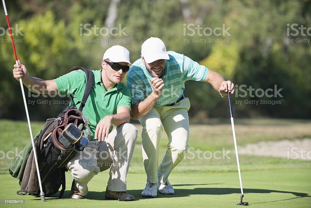 Golfer And Caddy Contemplating A Putting shot stock photo