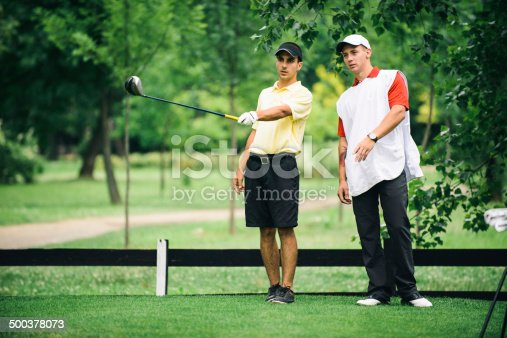 Golfer and caddy talking on the tee box. Toned image
