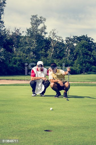 Golfer and caddy, contemplating putting shot. Toned image