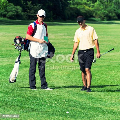 Golfer and caddy on the golf course, ball lying in rough.