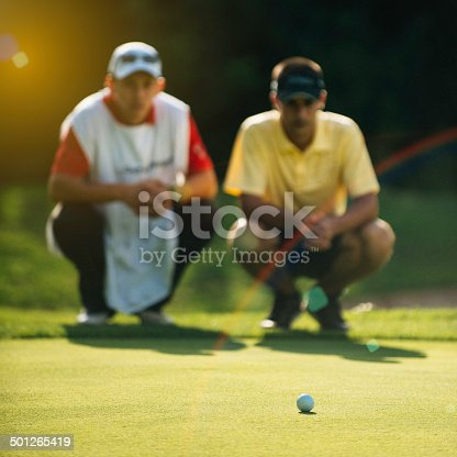 Golfer and caddy reading green. Golf ball in focus, toned image
