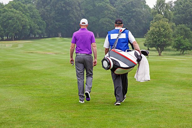Golfer and caddy walking up a fairway stock photo