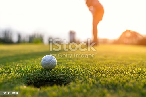 istock Golfer asian woman putting golf ball on the green golf on sun set evening time, select focus. Healthy and Lifestyle Concept. 887491304