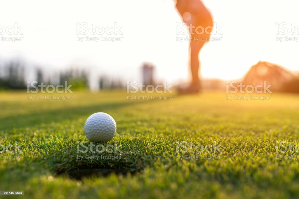 Golfer asian woman putting golf ball on the green golf on sun set evening time, select focus. Healthy and Lifestyle Concept. stock photo
