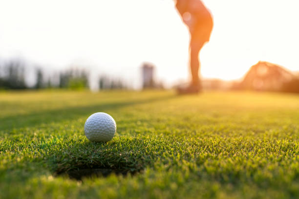 golfer asian woman putting golf ball on the green golf on sun set evening time, select focus. healthy and lifestyle concept. - golf stock photos and pictures