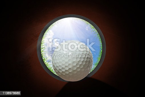 Golfer at golf ball view from inside the hole of cup in the green golf and lens flare on sun set evening time or blue sky background.
