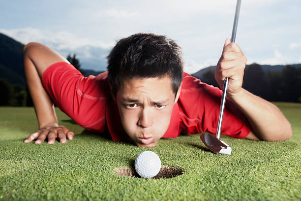Golfer blowing ball into cup. stock photo