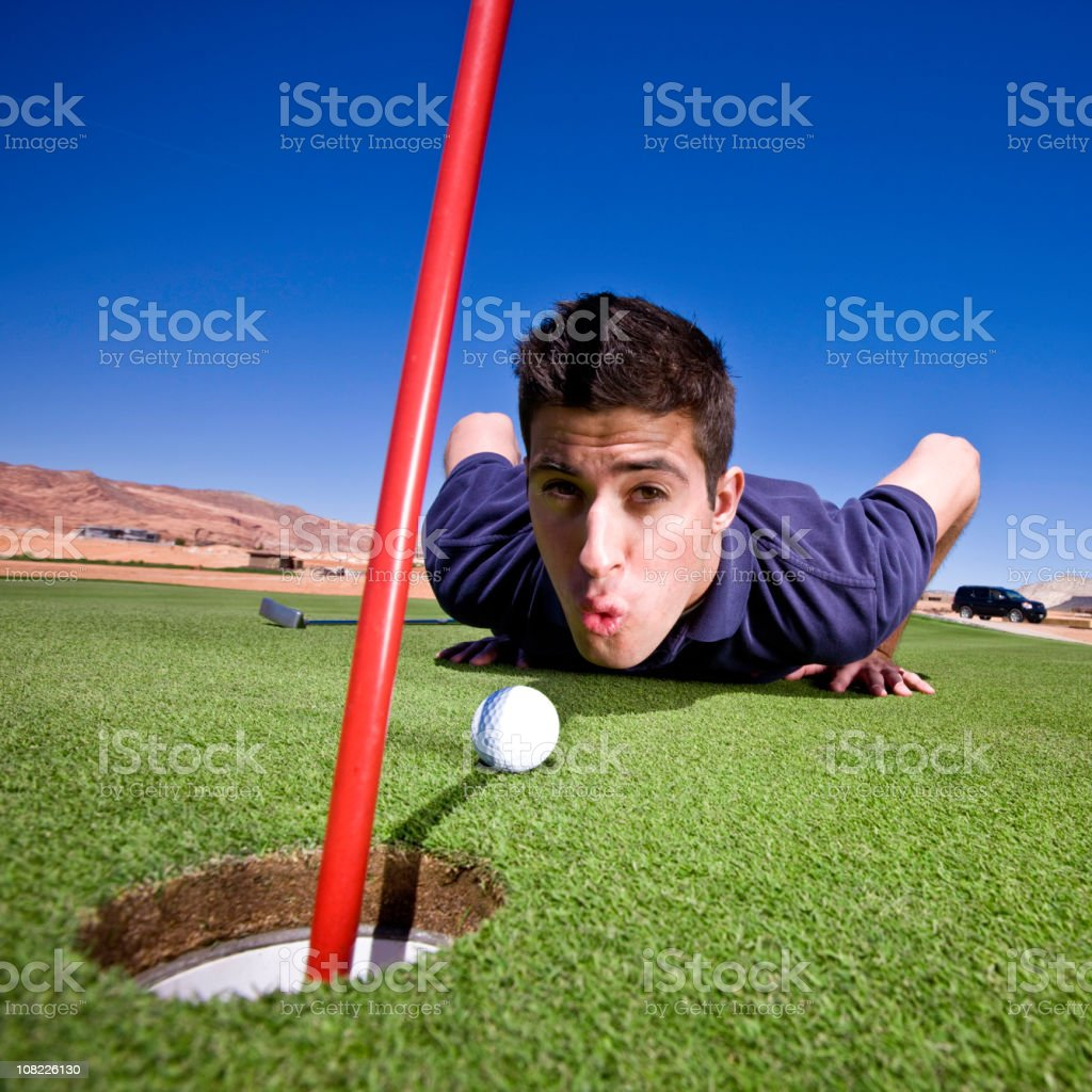 Golfer Blowing Ball into Hole royalty-free stock photo