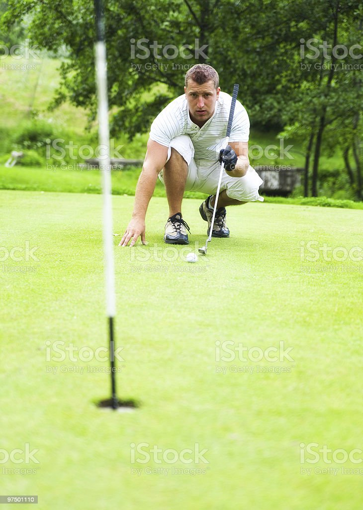 Golfer checking distance to hole royalty-free stock photo