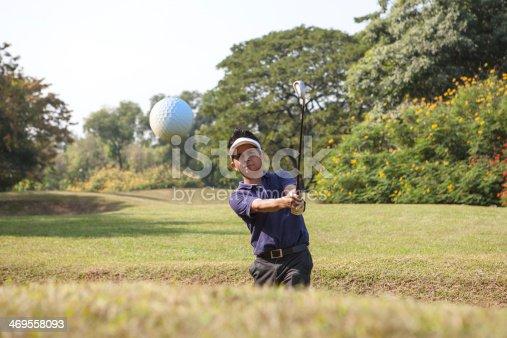 istock Golfer chipping golf ball out of a sand trap 469558093