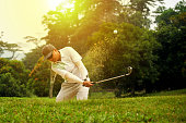 Image of Golfer Chipping out of Sand Trap.