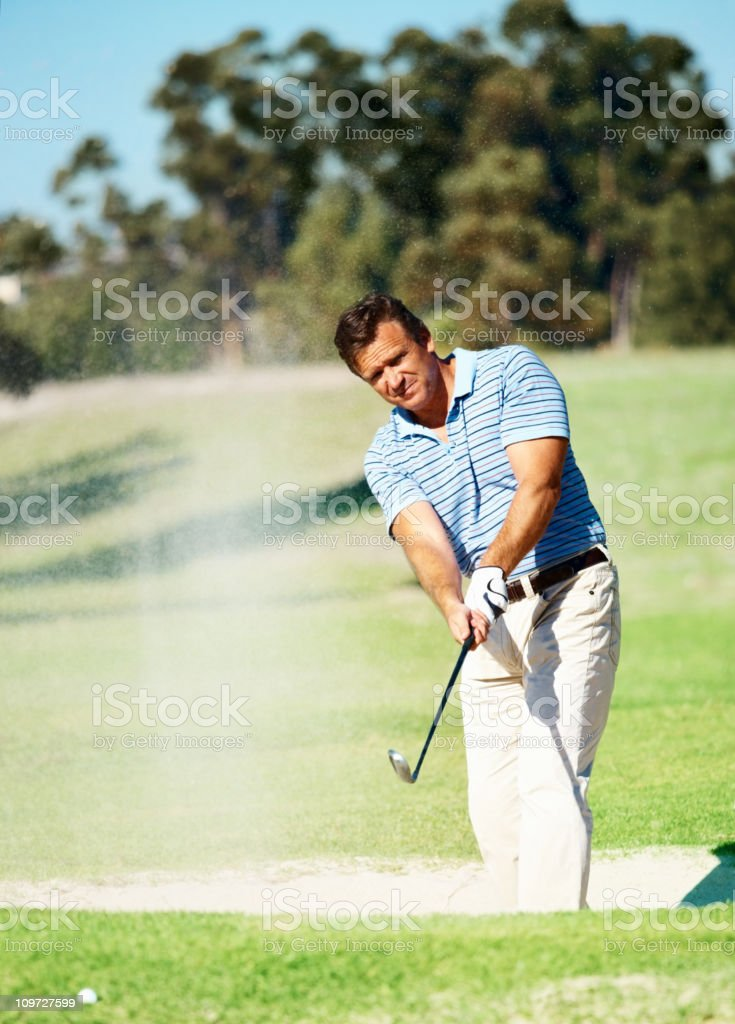 Golfer chipping the ball out of a sand trap royalty-free stock photo