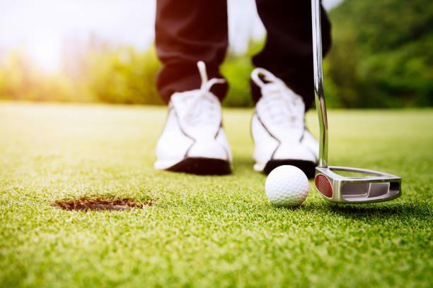 Golfer-Fokus setzen Golfball ins Loch. – Foto