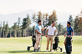 Multi-ethnic group of young men walking on a golf course
