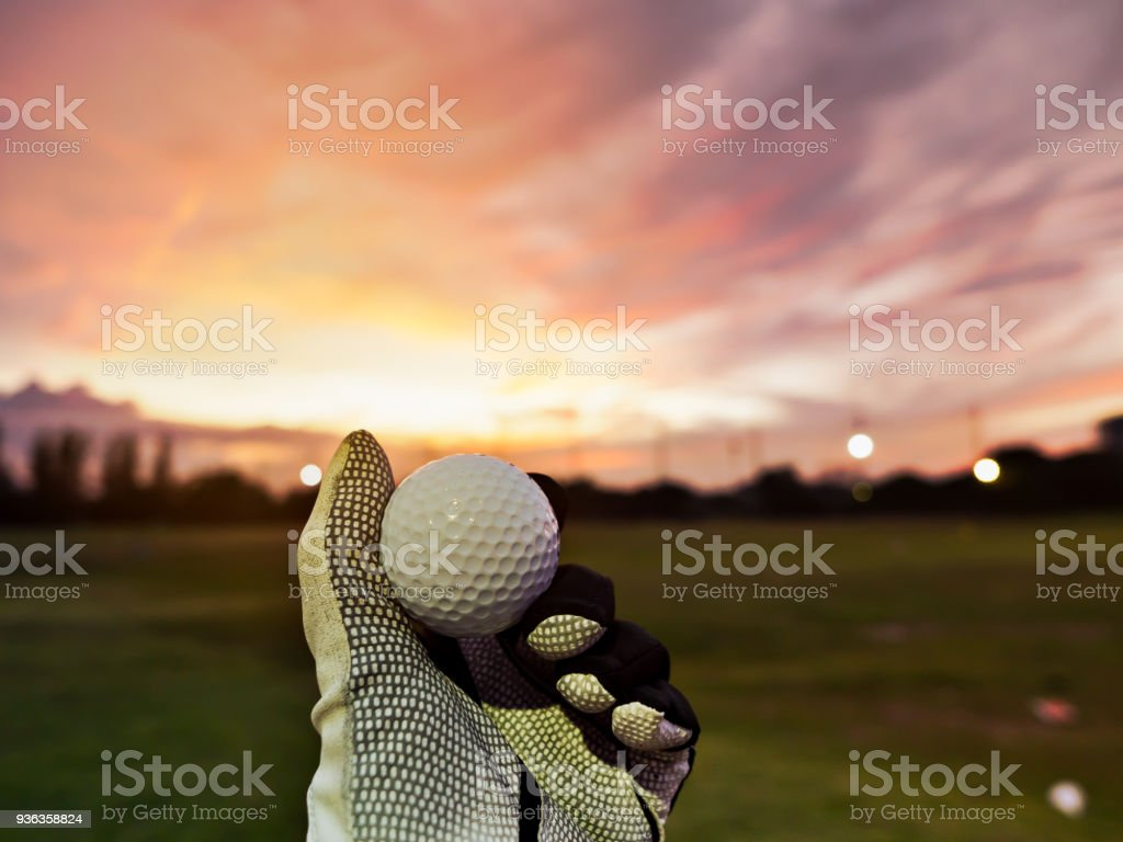 Golfer hand wearing golf glove and holding golf ball on fairway or tee off in the morning with beautiful sunrise sky background for start golf round stock photo
