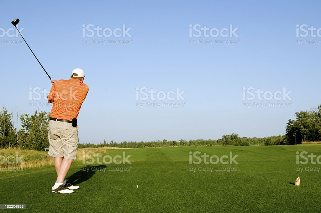 Golfer hits ball down fairway royalty-free stock photo