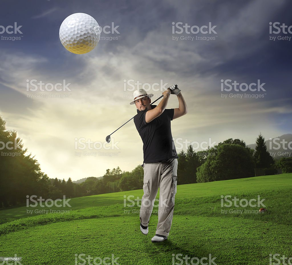 Golfer hitting a golf ball towards the camera royalty-free stock photo
