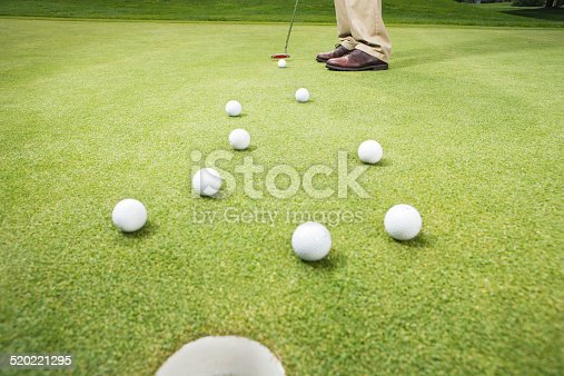Golfer hitting ball through group of golf balls, low section