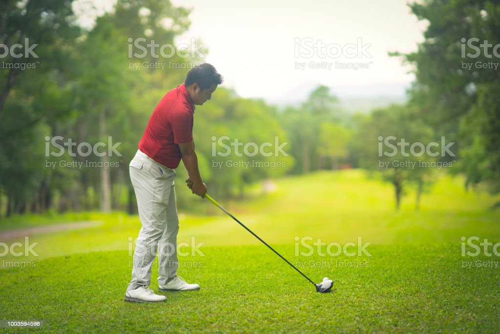 Golfer hitting golf ball on tee off in golf course