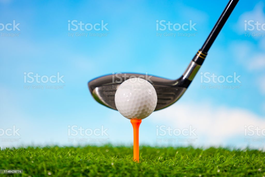 Golfer hitting golf ball on tee on grass on blue sky and white...