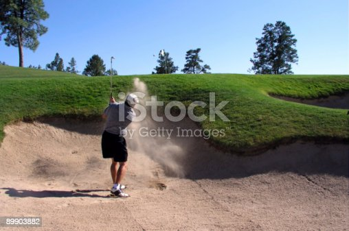 istock Golfer hitting golf ball out of sand trap 89903882