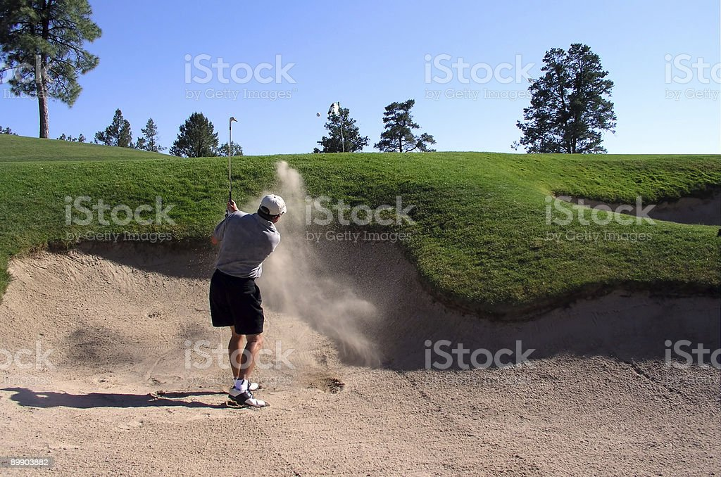 Golfer hitting golf ball out of sand trap stock photo