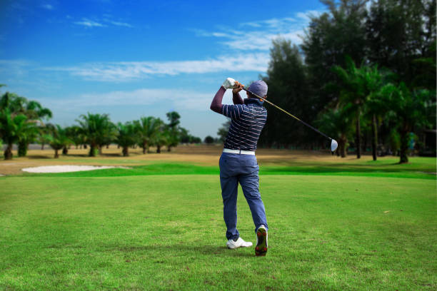 golfer hitting golf shot with club on course vintage color tone, man playing golf on a golf course in the sun, golfers hit sweeping golf course in the summer. - golf foto e immagini stock