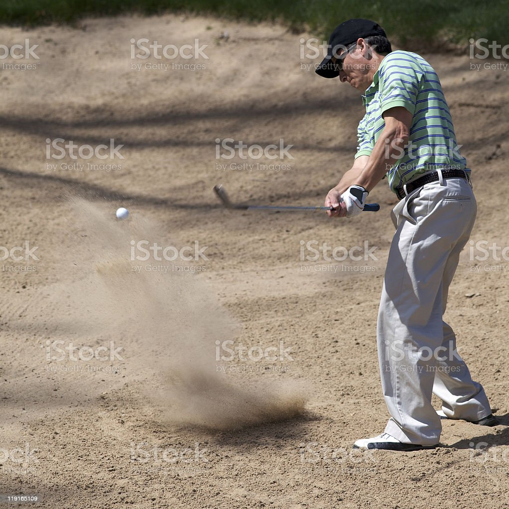 Golfer hitting out of sand trap royalty-free stock photo