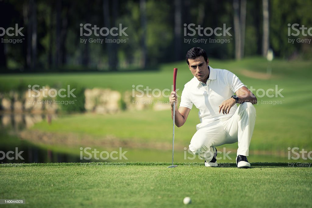 Golfer holding club in hand and watching ball rolling royalty-free stock photo