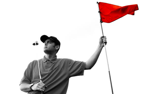 Golfer in black and white holding a red flag stock photo