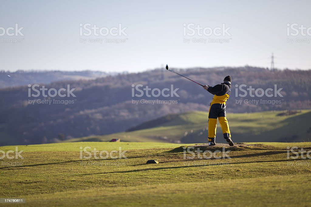 Golfer in winter clothing drving from a tee stock photo