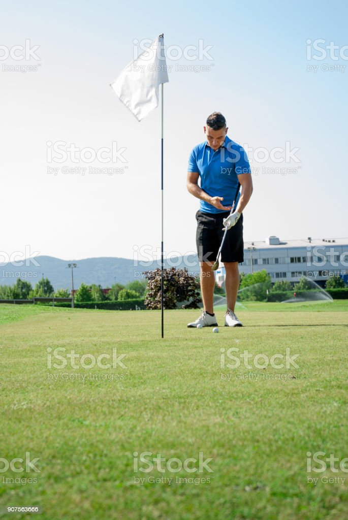 Golfer Inspecting the Golf Club Near the Hole Before Potting the Ball stock photo