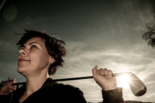 Golfer Leaning Her Golf Club on Her Shoulders with Sunlight stock photo
