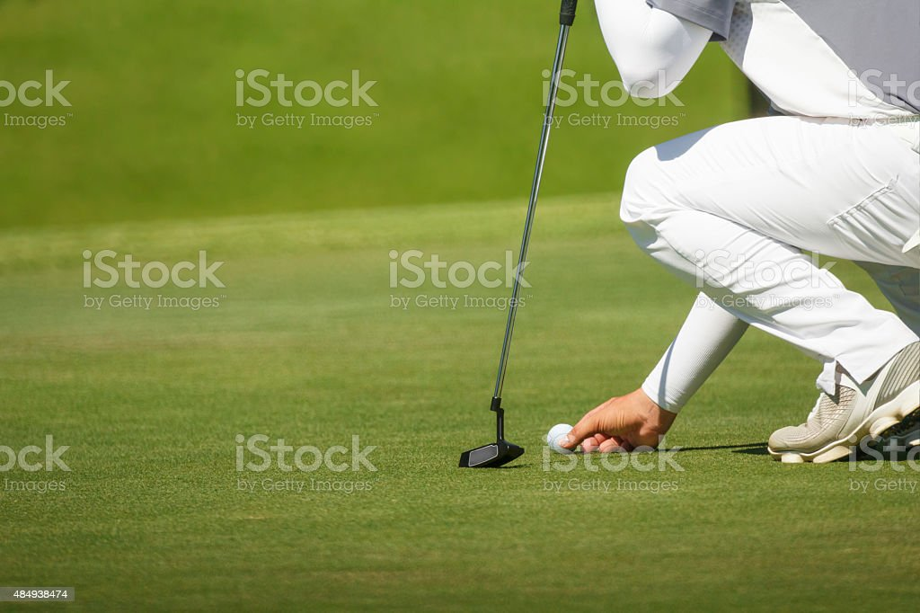 golfer marks his position on a green stock photo