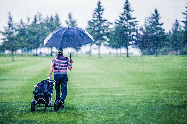 golfer on a rainy day leaving the golf course - drenched stock pictures, royalty-free photos & images