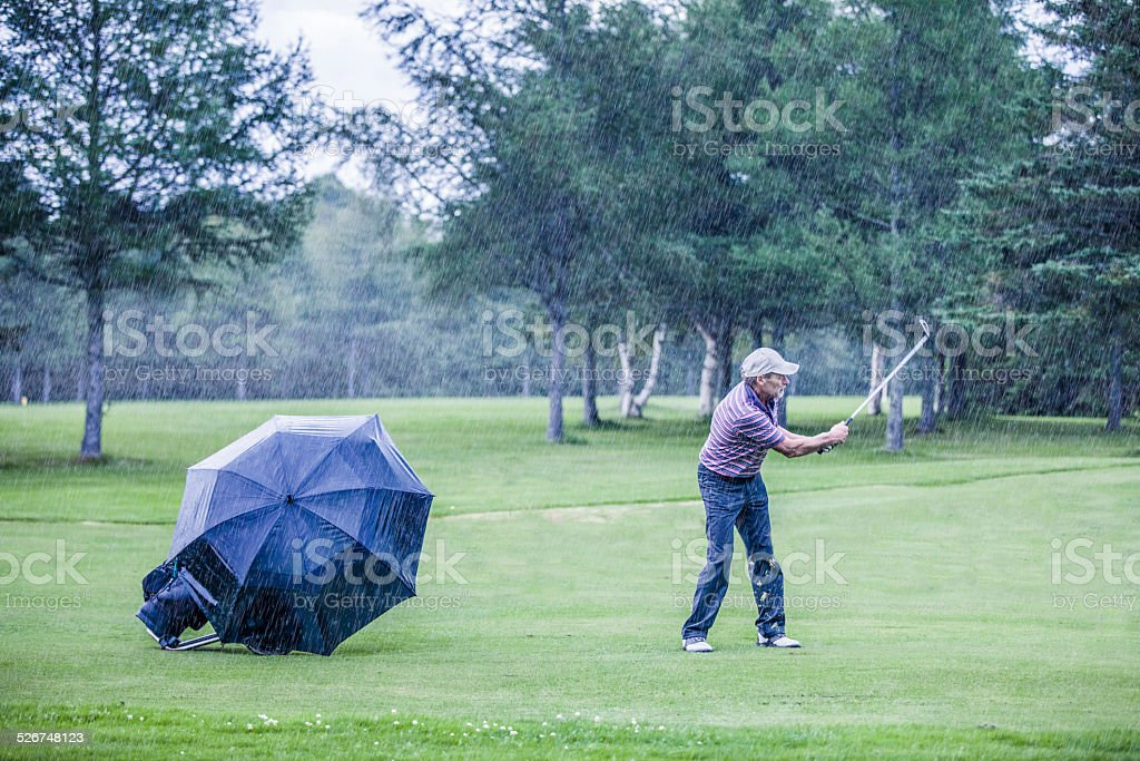 Golfer on a Rainy Day Swigning in the Fairway stock photo