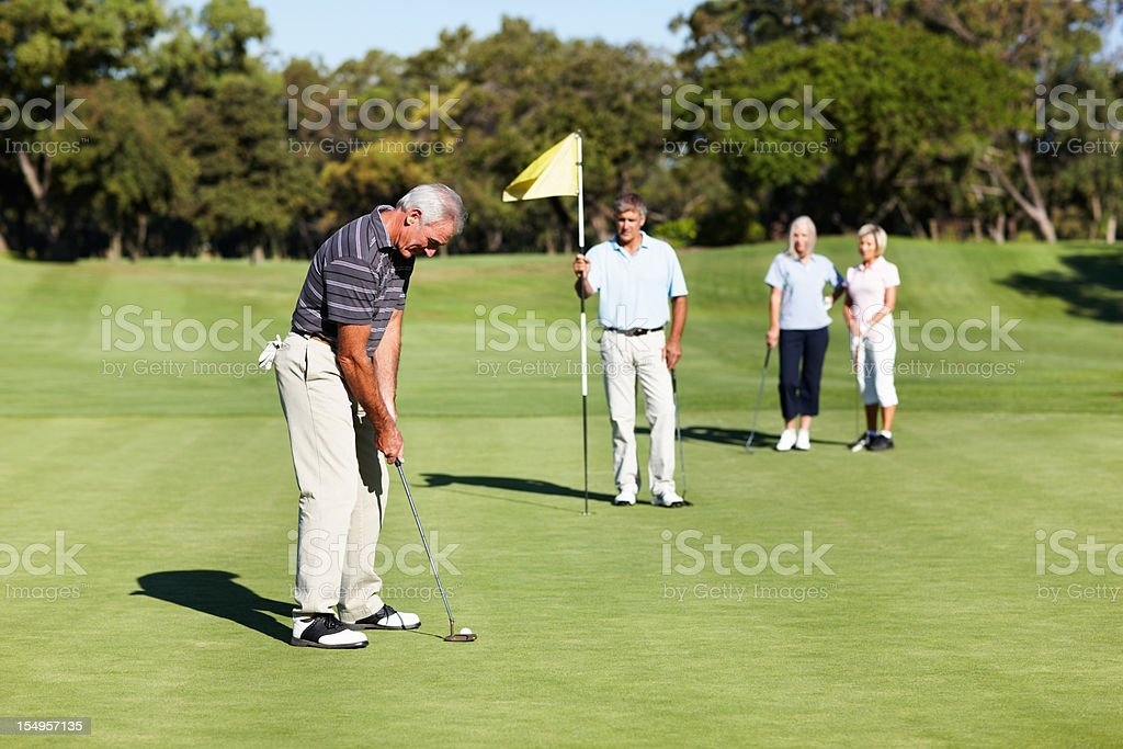 Golfer on green putting the golf ball royalty-free stock photo