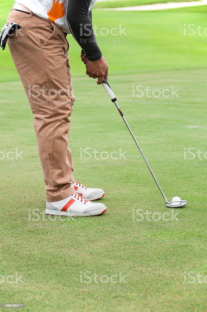 Golfer on putting green.