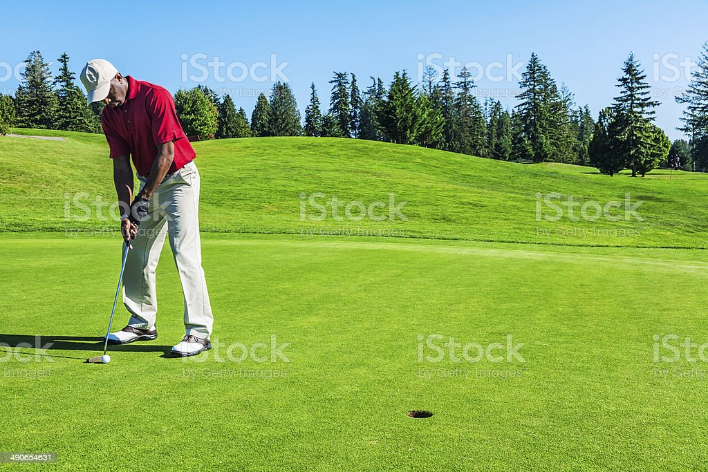 Photo of a golfer on putting green, preparing to sink his ball in the...