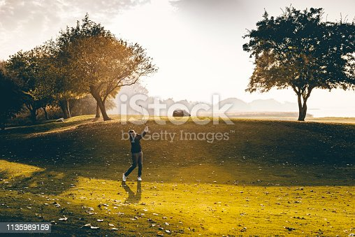 Male golfer taking a shot from the fairway. Colour, horizontal with lots of copy space. Photographed on a golf course on the island of Møn in Denmark.